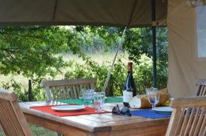 wijn, stokbrood en kaas op de veranda van je safaritent